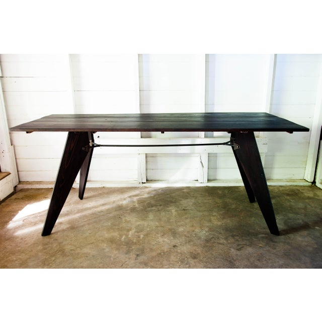 The vintage wood, handmade mid-century 1950 utility dining table in black features aerodynamic lines, minimalist joinery,...
