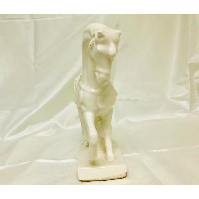 White crackle glazed statue of a regally poised horse in Chinoiserie style. Made in the 1970s.