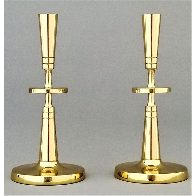 Offering a tall and elegant pair of high-polished brass candlesticks designed by Tommi Parzinger for Dorlyn Silversmiths,...