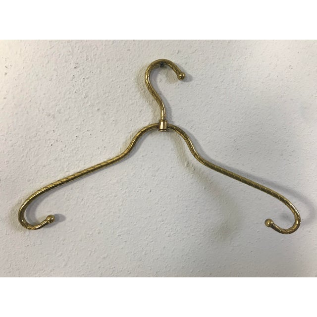 This is a charming vintage brass clothes hanger. It is a lovely, sturdy hanger for coats, outerwear, or any piece of...