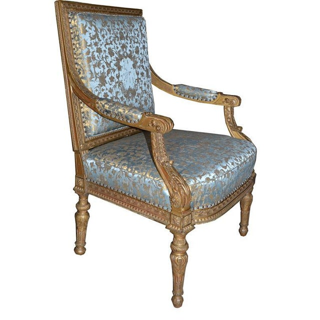 Pair of very finely carved French giltwood armchairs with newly upholstered Rubelli blue and gold fabric.