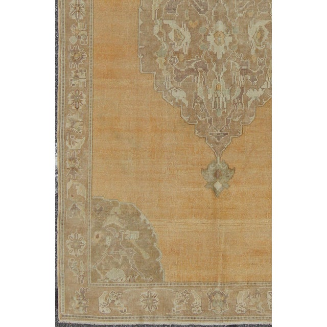 This vintage Turkish Oushak rug (circa mid-20th century) features a unique blend of colors and an intricately beautiful...