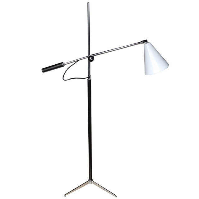 This Italian one-arm lamp moves up and down the central bar. It sits on a tripod base made of chrome, and has a white...