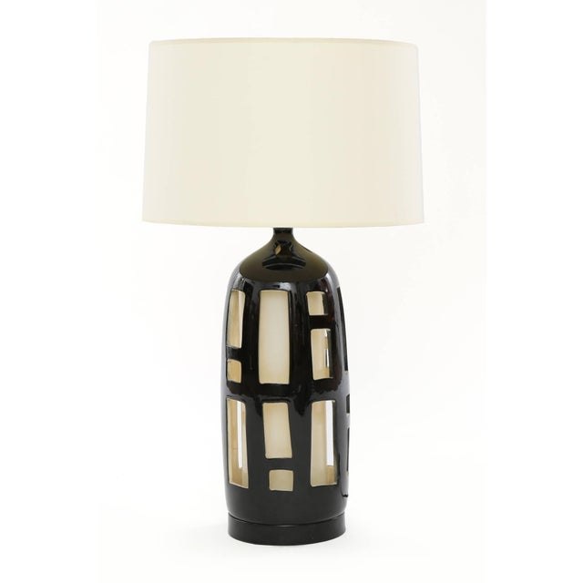 Striking pair of cut-out ceramic lamps from the early 1970s. These examples have black glazed forms with linen interiors...
