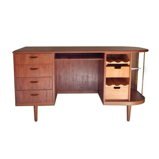 Mid-Century Scandinavian teak desk with a full bar behind a sliding tambour door. Two drawers, two wine racks and two...