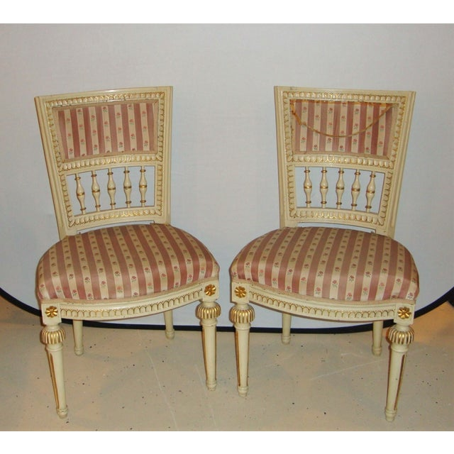 An elegant pair of paint decorated side chairs in the Maison Jansen style. Seat height: 18 inches