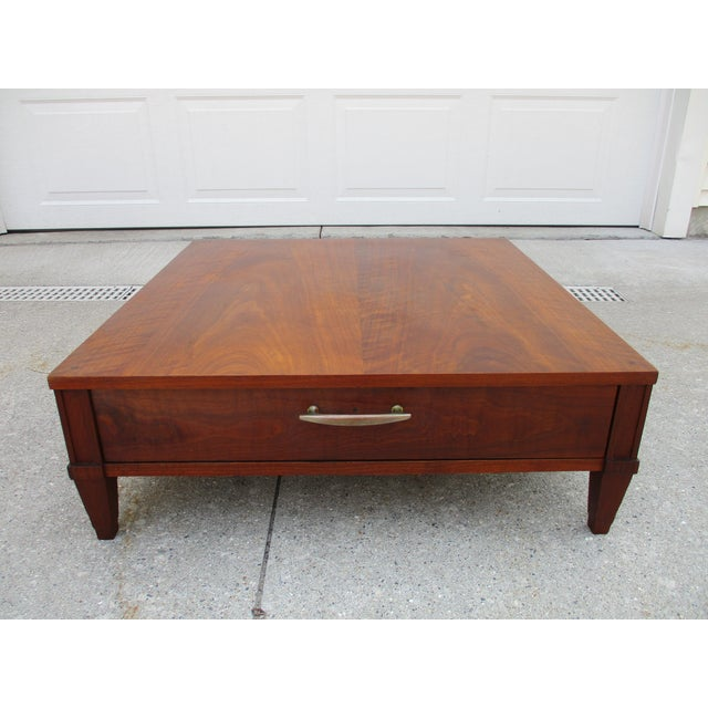 A great low walnut side table by Baker Milling Road. This table features one drawer will a large brass pull. The table is...