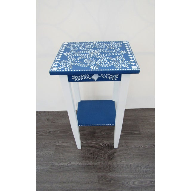 Hand Painted accent table in white and blue with a Moroccan Design Top. The Table has an additional shelf. This sweet...