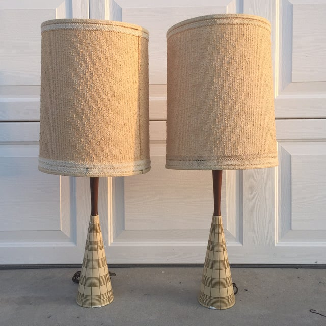 A pair of mid century modern walnut and ceramic table lamps.