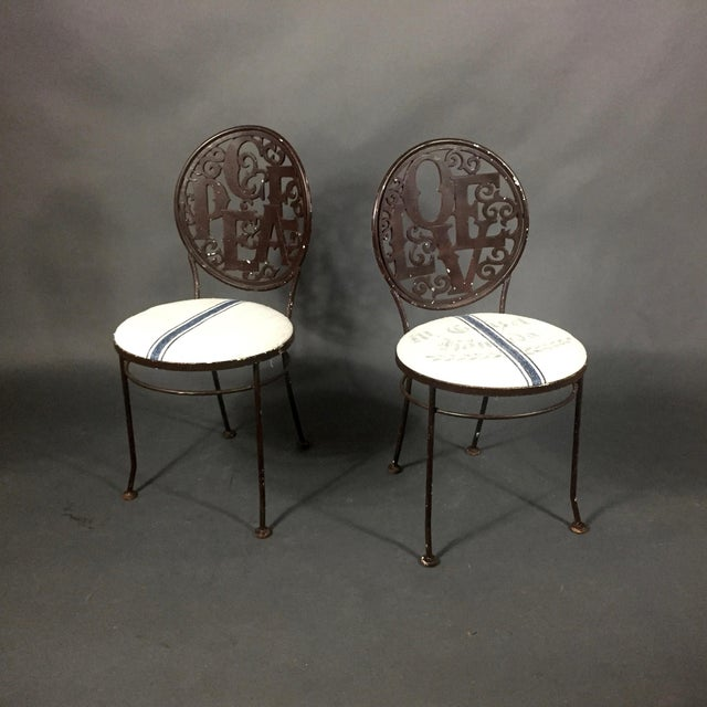 Early cast iron garden chairs with PEACE and LOVE on backs, both painted in brown with original pad feet. Recently updated...