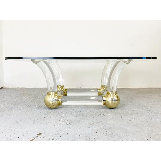 Stunning lucite tusk and brass ball coffee table. Elegant and striking; a great statement piece.