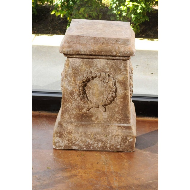 A pair of continental faux stone garden plinths with wreath décor from the mid-20th century. Each of this pair of garden...
