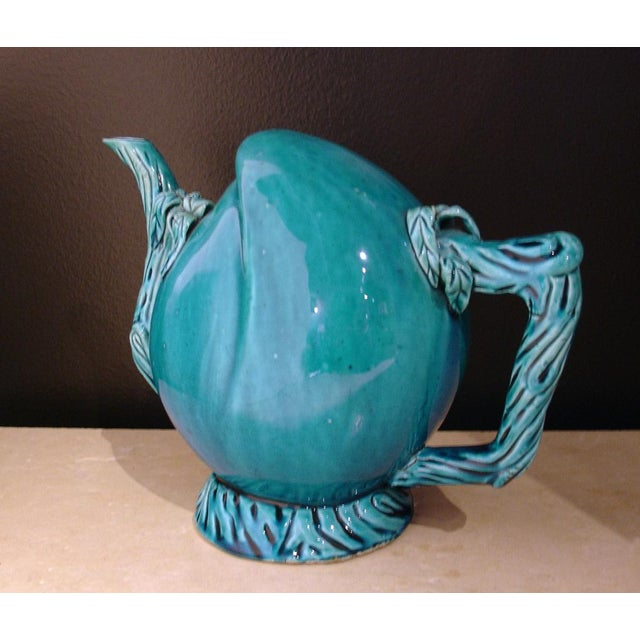 A Cadogan wine or tea pot shaped as a peach, with the handle and spout molded as intertwining branches. The entire pot...