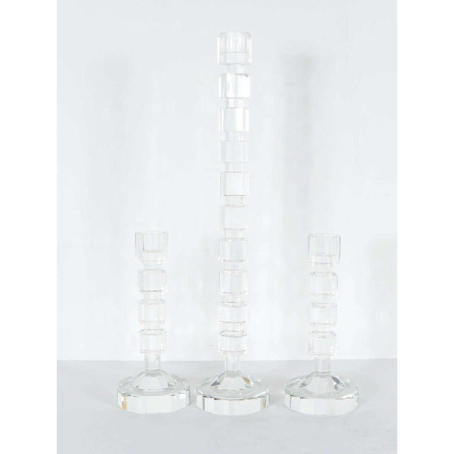 These set of three candleholders feature a geometric Art Deco style in cut crystal . They are columnar if form with cut...