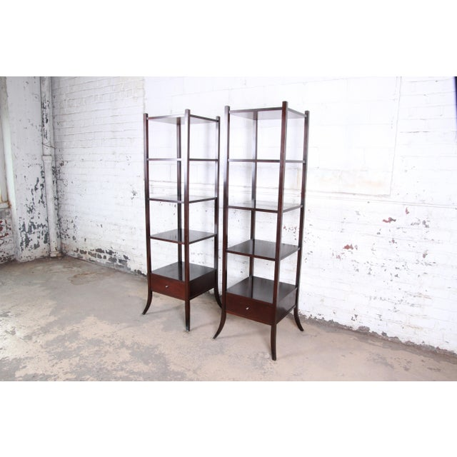 A gorgeous pair of dark mahogany etageres designed by Barbara Barry for Baker Furniture. The etageres feature clean,...