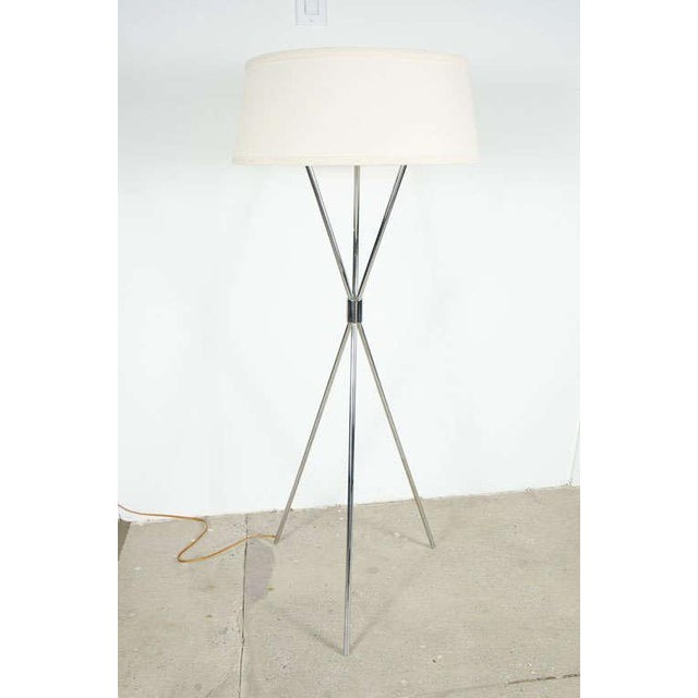 A floor standing reading lamp comprising three polished chrome poles that intersect at a solid cylindrical hub, with three...