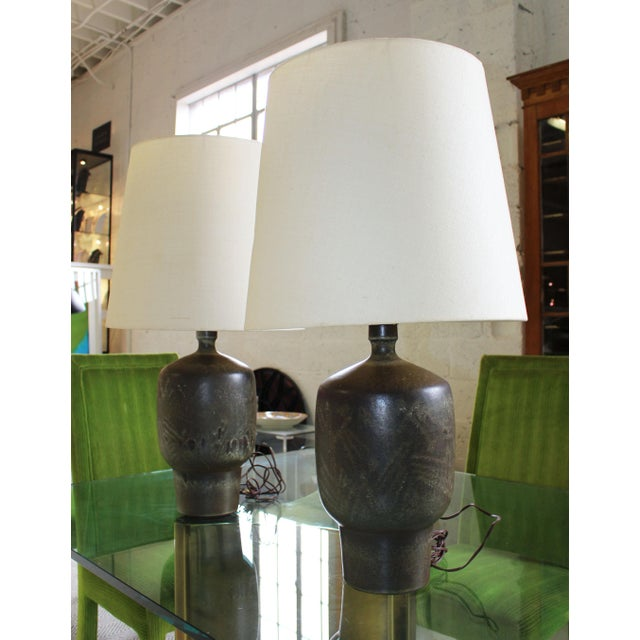 Wonderful rare pair of 3 bulb pottery table lamps by Lee Rosen for Design Technics. The lamps feature a stunning graffito...