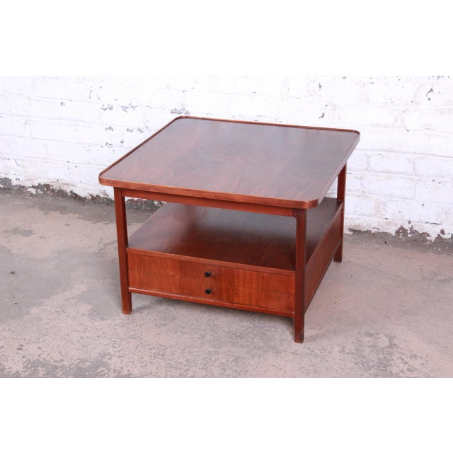 A gorgeous mid-century modern rosewood two-tier cocktail table or occasional table by Jack Cartwright for Founders. The...
