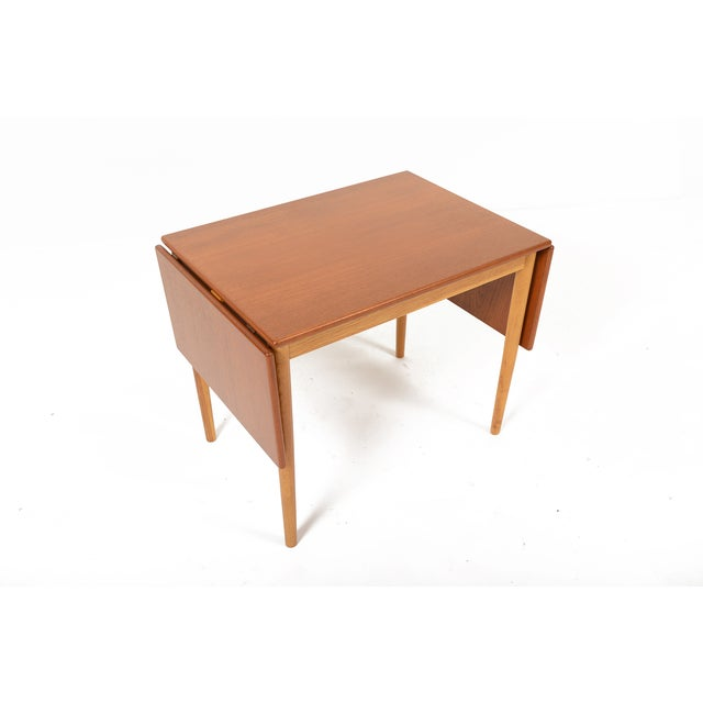 Danish Mid-Century Modern drop leaf extension coffee table in teak and oak designed by Børge Mogensen. A beautiful teak...
