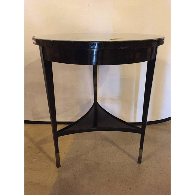 An ebonized silver gilt mirror top centre or end table. On bronze sabots having tapering legs with a lower triangular...