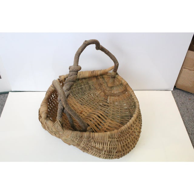 Handwoven folk art basket with branch handle.