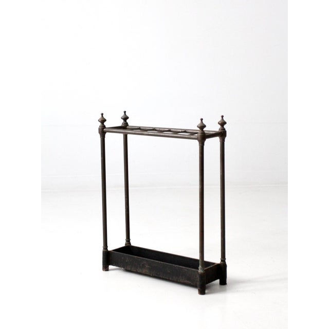 This is an antique brass and cast iron fireplace or umbrella stand. The stand features a cast iron basket base with brass...