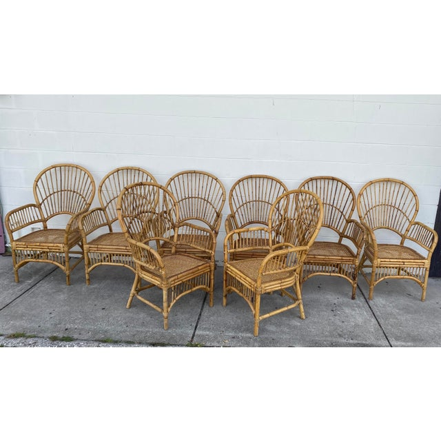 Vintage set of 8 rattan fan back arm chairs. Pencil reed backs with triple band trim around seats. The sturdy frames have...