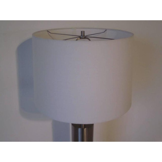 A brushed stainless table lamp with bone white linen shade manufactured by the Laurel Lamp Company.