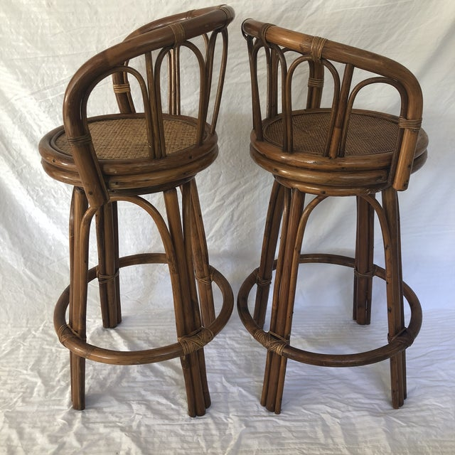 This pair of mid-century bamboo swivel barstools with rattan seats is in excellent original vintage condition. All the...