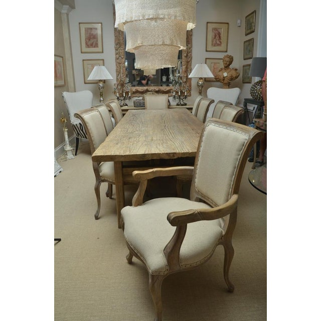 Antique elm country dining table with ten chairs. There are two armchairs and eight side chairs. The chairs are limed oak...