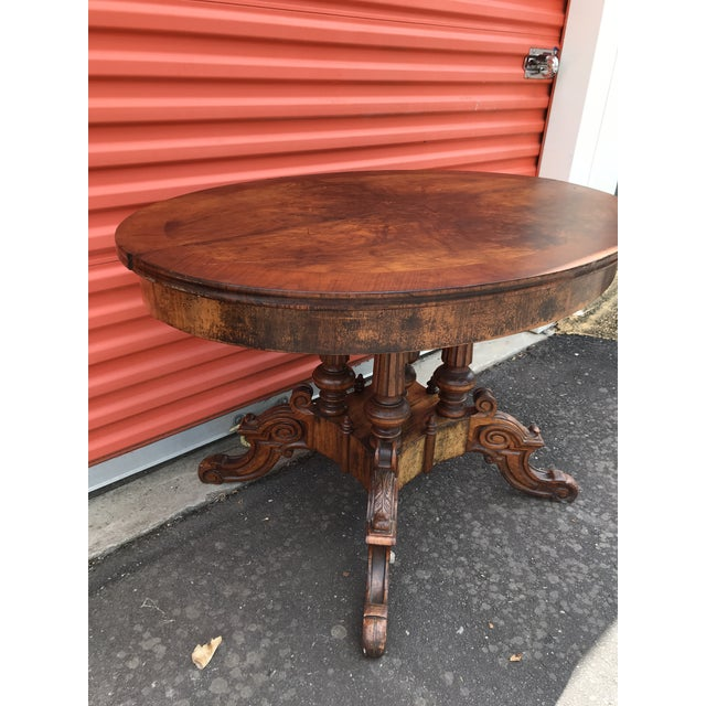 Antique oval flame mahogany side table with carved pedestal base.