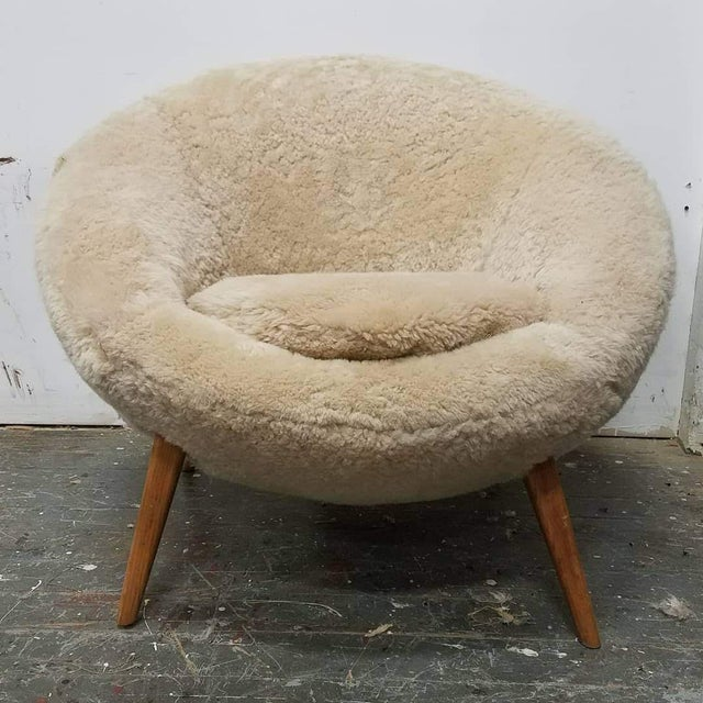 """Mid century Jean Royere style """"ouef"""" chair recovered in sheepskin pelts. Oak legs have been refinished."""