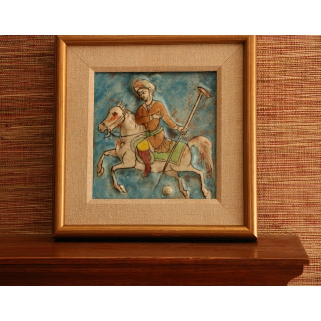 Exquisitely decorated square Qajar tile featuring a polo-playing horseman in relief. The glaze is uneven and worn,...
