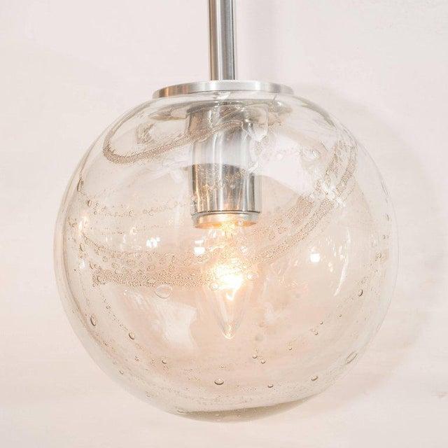 This sophisticated pair of globe pendants were realized by the esteemed German lighting studio, Doria Leuchten, circa...