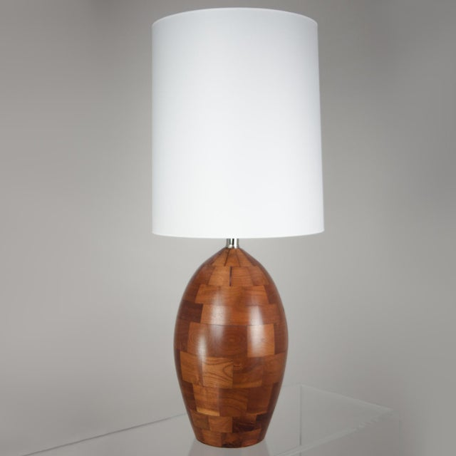 Egg shaped walnut lamp made of staved walnut blocks with clear satin finish. Professionally rewired with black silk cord...