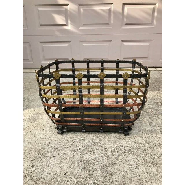 A very large and heavy hand hammered copper, brass and iron decorative basket featuring brass owl adornments on the...