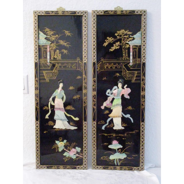 Beautiful set of two midcentury Japanese black lacquered wood wall panels, each depicting a geisha, flora and pagoda...