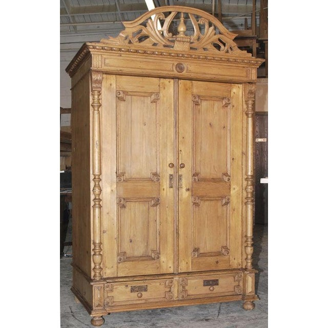 This 19th century armoire with extensive carvings, turnings and decorative moldings has two drawers. This piece is...