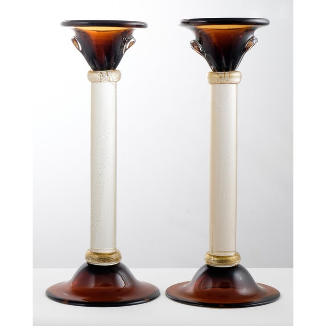 """Murano glass pair of candlesticks with """"avventurina"""" glass columns and rings, deep amber tops and bases. Signed Davide..."""