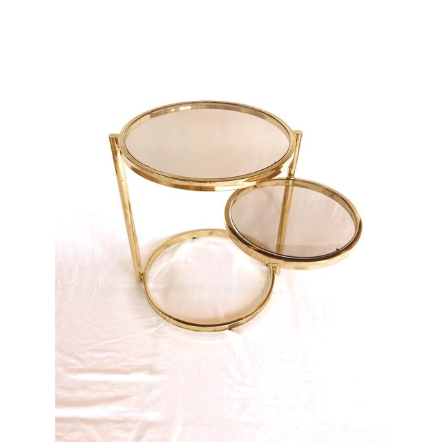 Mid-Century Modern two-tier side table with extendable top. Brass frame with adjustable and rotating second tier allowing...