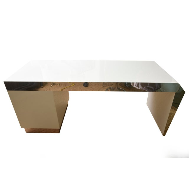 This angled and wonderful white lacquered wood desk has stainless steel apron banding and base banding. There are 3 file...