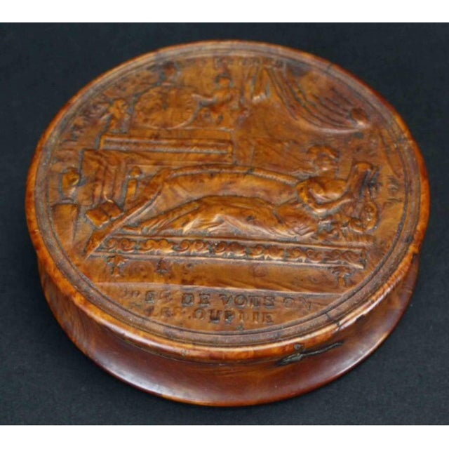 The circular lidded box depicting a woman reclining on a Recamier playing the harp. The underside with a star surrounded...