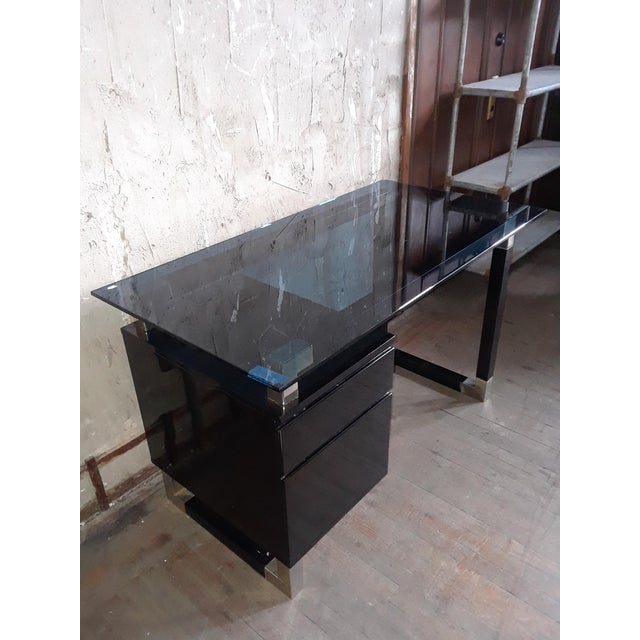 This beautiful desk has a lacquered black paint and a blue glass top, as well as enough storage space, making it both...