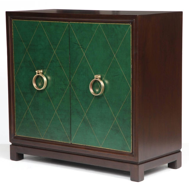 Classic Mid-Century Walnut cabinet with tooled diamond patterned green leather door panels and satin brass door knocker...