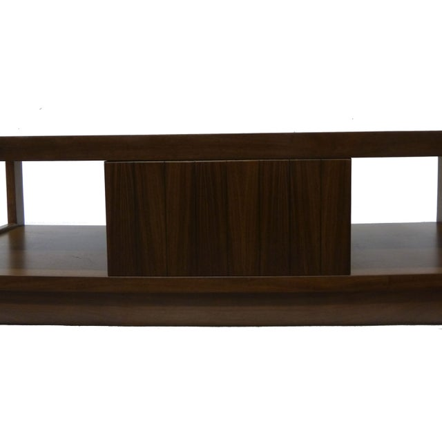 This highly structured, mid-century modern coffee table by Lane is rendered in walnut and brass and features plenty of...