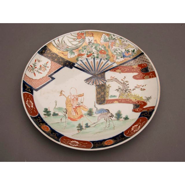 An Imari charger from Arita, Japan c. 1875 featuring a scholar reading a scroll in a landscape surrounded by three cranes....