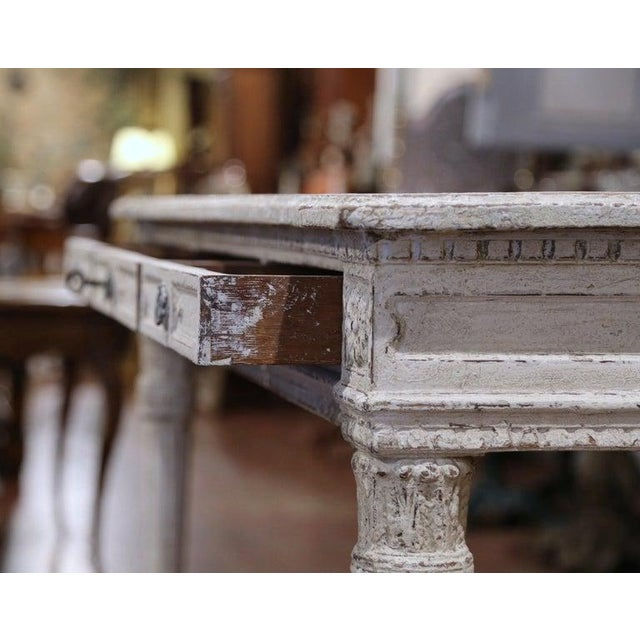 This elegant antique console was created in France, circa 1870. The grey painted table sits on four carved and tapered...