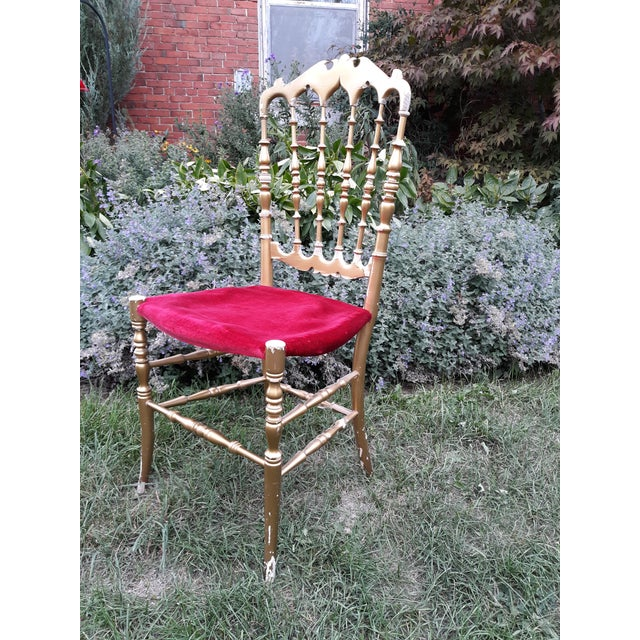 This is a classic Italian Chiavari chair in wood with gold and velvet. The chair has some chipping to the gold. It is rock...