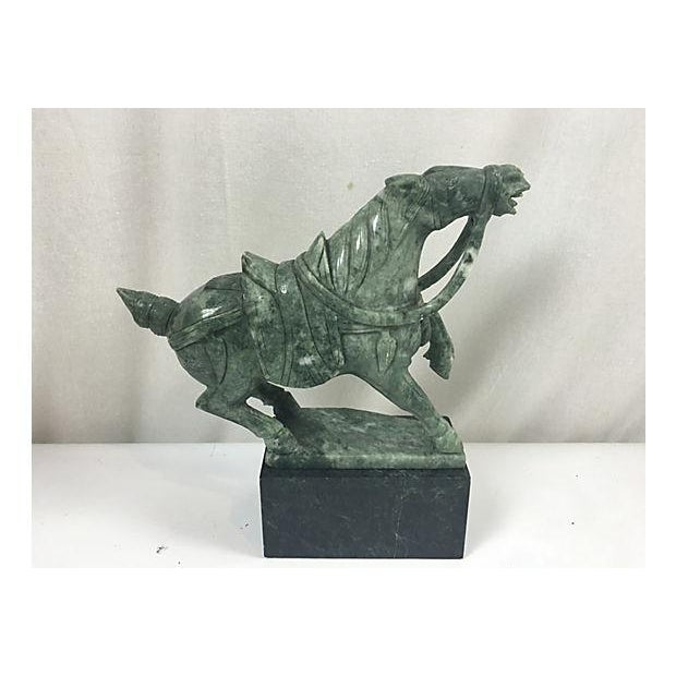 Offered is a jade hand carved horse over a marble base sculpture. No signature.