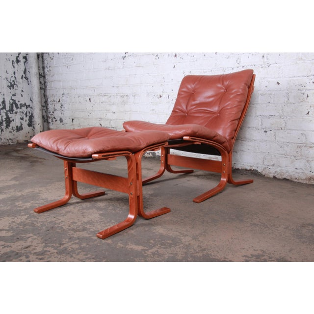A sleek and stylish minimalist Scandinavian Modern bentwood teak and cognac leather lounge chair and ottoman By Ingmar...